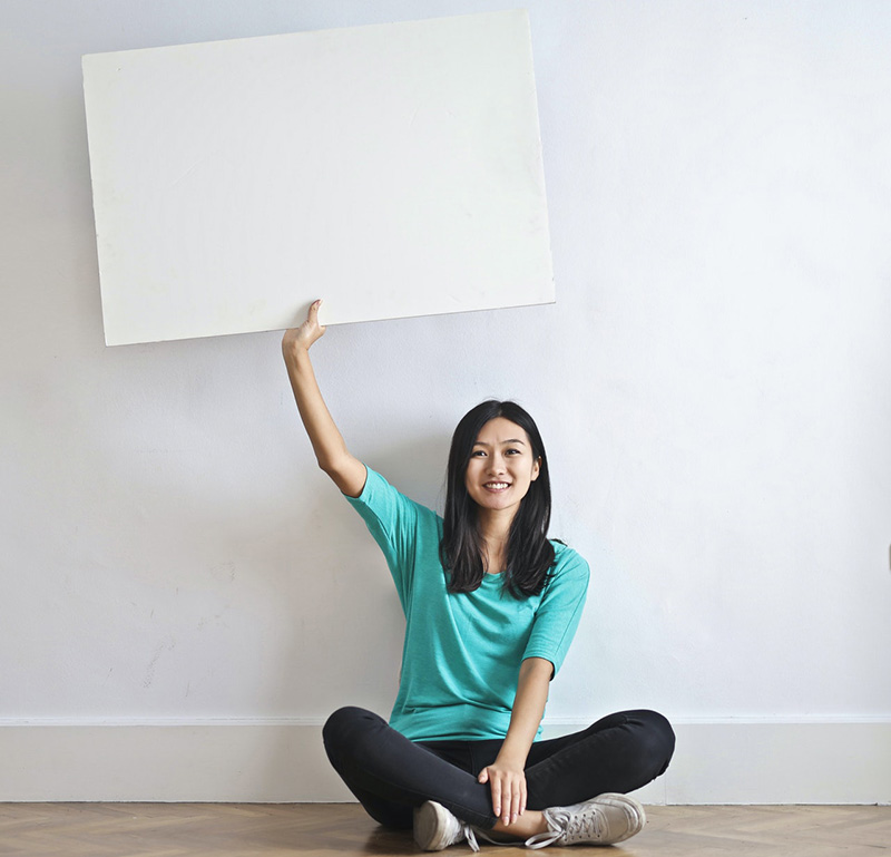 Smiling woman with blank poster in empty flat