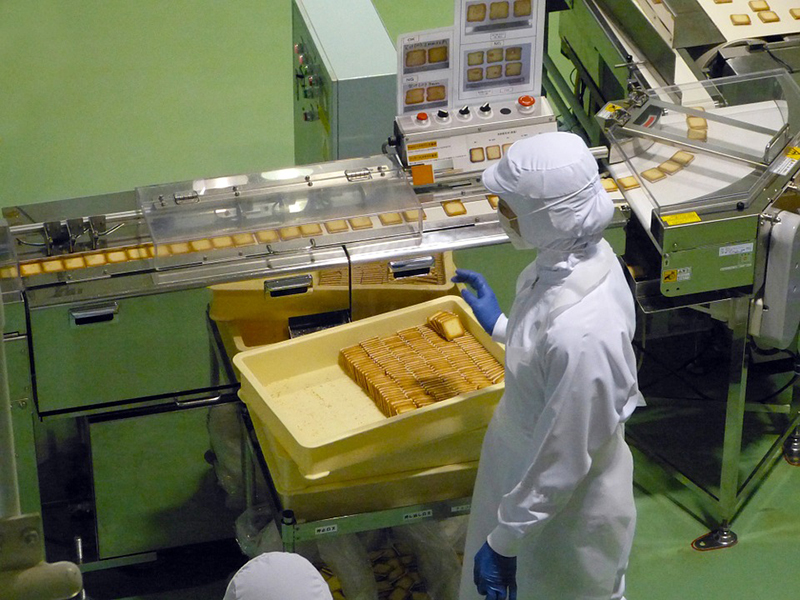 Person wearing white jumpsuit inside the Manufacturing plant