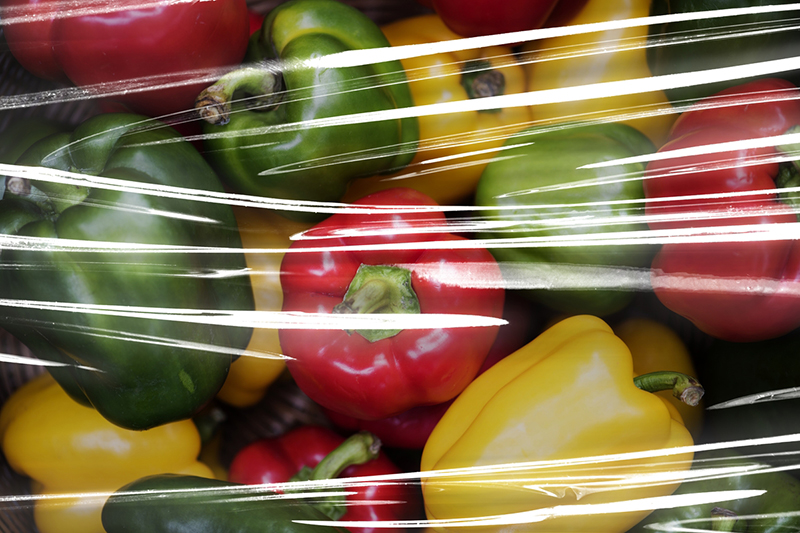 Fresh bell peppers covered with plastic wrap