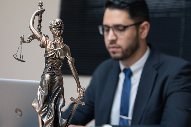 a lawyer behind a justice figure statue