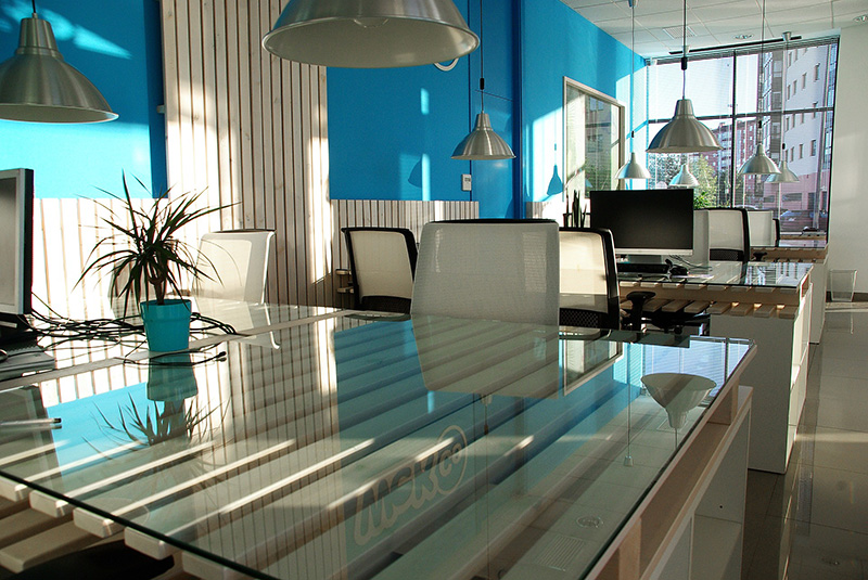 Office space with white chairs and glass table