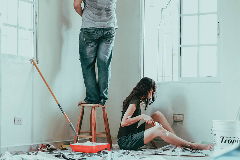 Man and woman painting the house wall