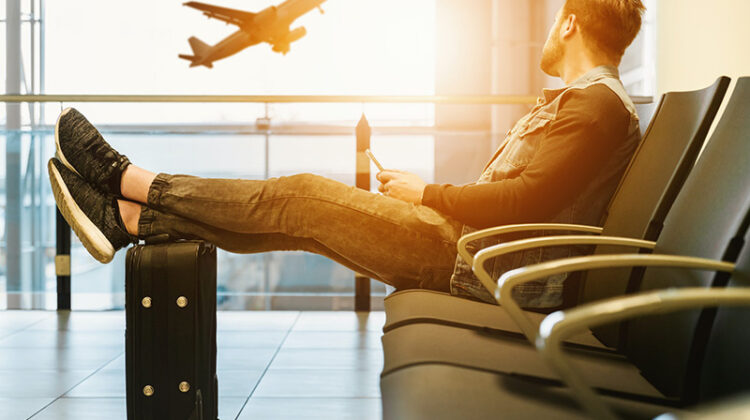 Man sitting on airport lobby with feet on luggage