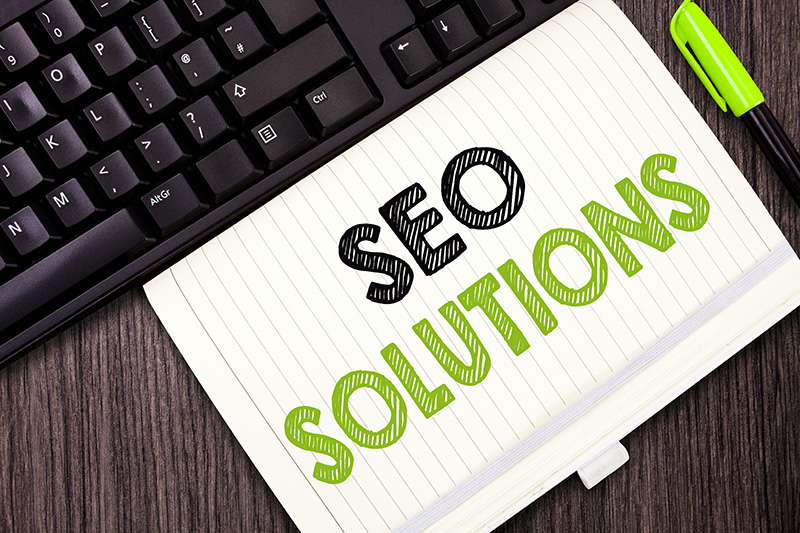 SEO solutions text on notepad near black keyboard