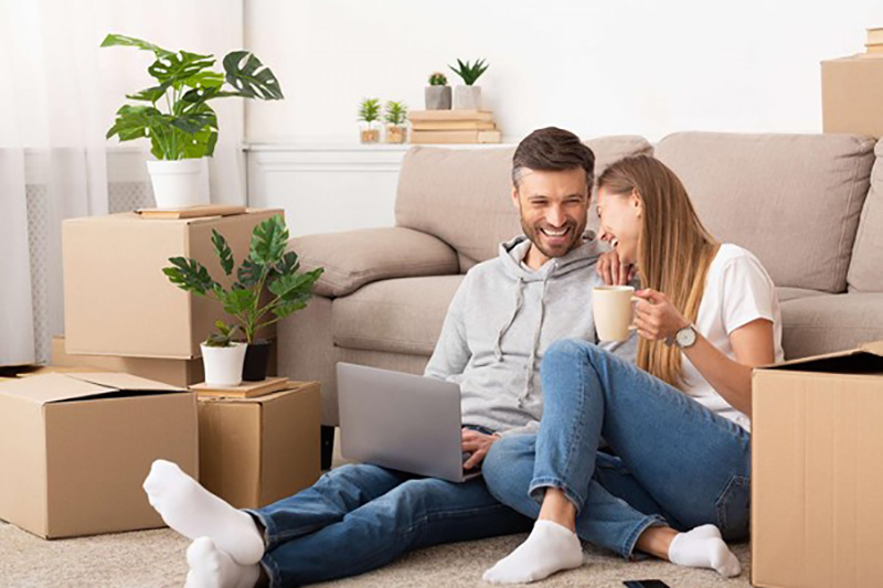Happy couple sitting on the floor near gray couch