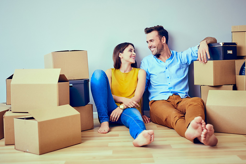 Couple sitting on the floor near brown boxes
