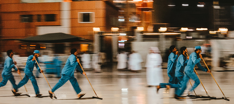 Blue-uniformed cleaners sweep a commercial space