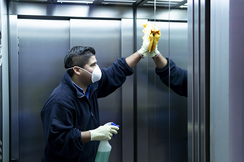 Cleaning staff disinfecting the elevator