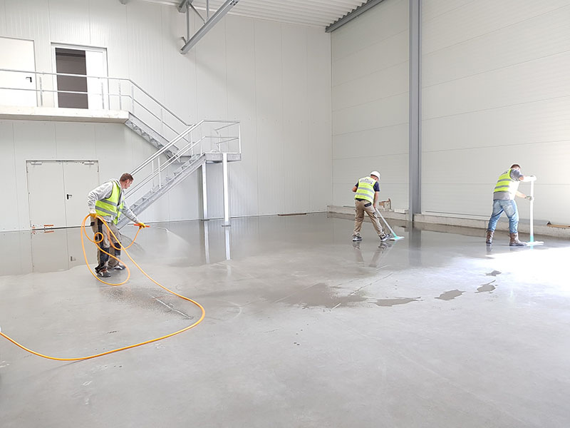 Workers wearing safety reflective vests cleaning the building floor
