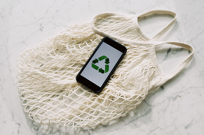 Mobile phone with green recycling symbol and mesh bag