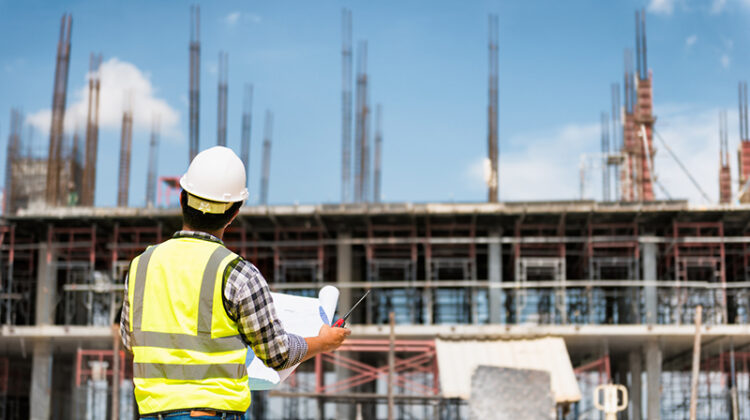 Engineering Consulting People on construction site holding blueprint in his hand.