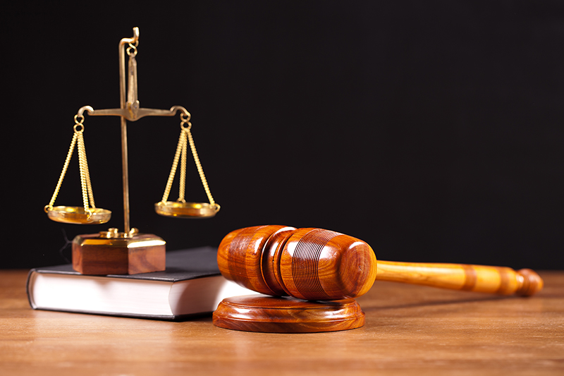 Gavel and book on top of wooden table