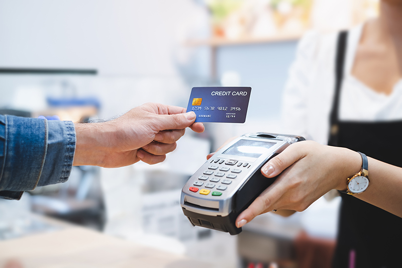 Customer using credit card for payment to owner at cafe restaurant