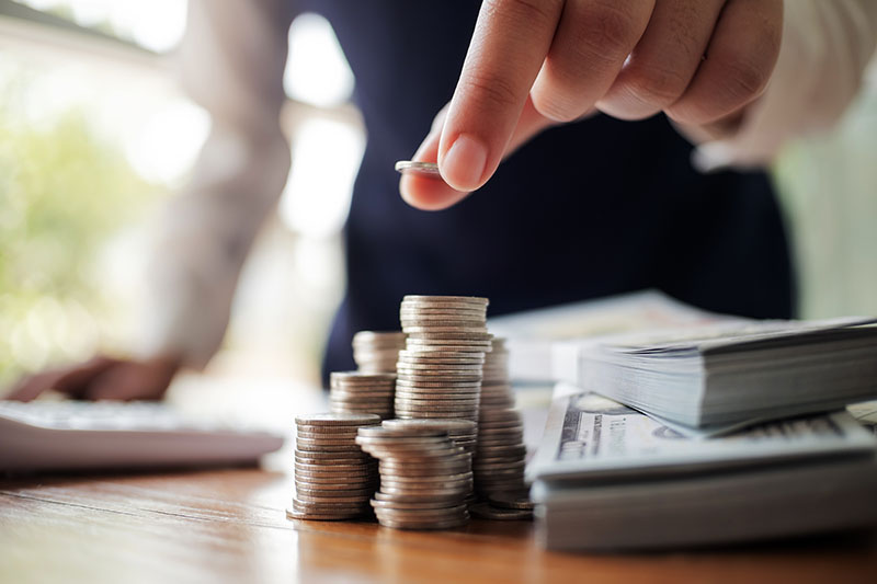 Business women put coin stack money and bank note in office