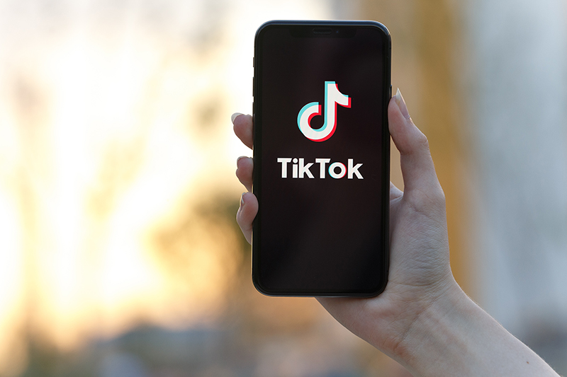 Tik Tok application icon on Apple iPhone X screen close-up.