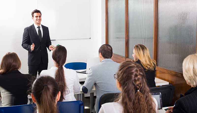 Group of attentive adult students with teacher in classroom at business training