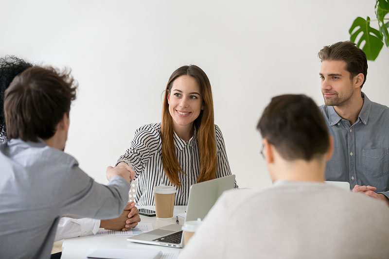 Smiling businesswoman shaking hand of male partner at the office meeting