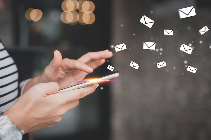 Woman hand using smart phone with email icon flying abstract