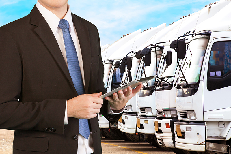 Businessman holding tablet standing over trucks in a row with Container background