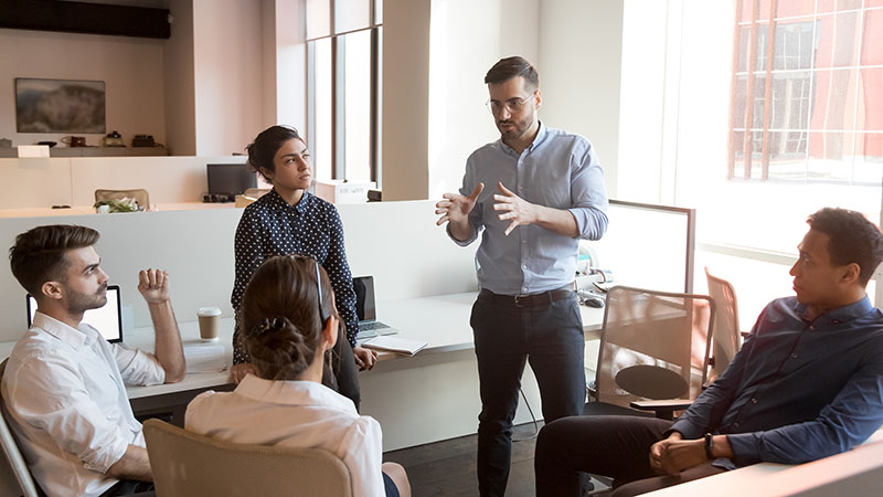 business man team leader coach mentor talk to diverse business people in office