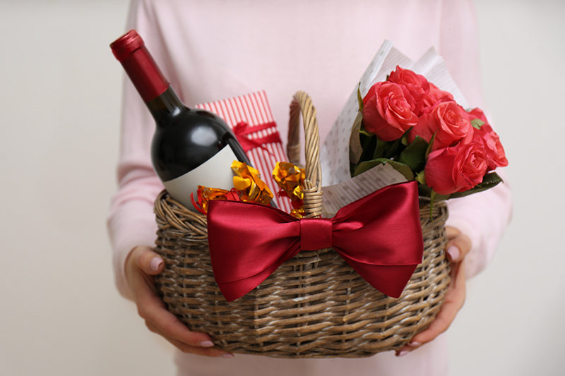 Woman holding wicker basket with gift, bouquet and wine