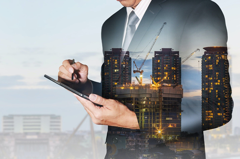a business man holding a tablet with buildings overlay in background