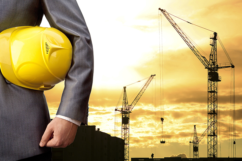 Businessman holding yellow helmet with construction site on the background