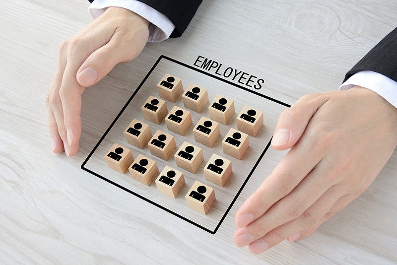 Wooden blocks with human pictogram surrounded by business man's hands
