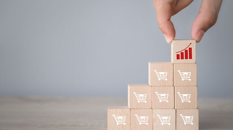 Hand arranging wood block stacking with icon Graph and shopping cart symbol