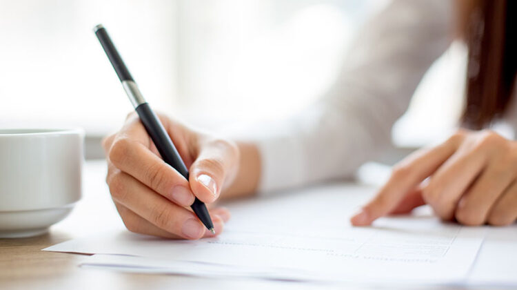 Hand of businesswoman signing on document