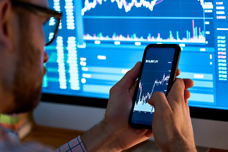 Business man trader investor analyst using mobile phone app analytics for cryptocurrency